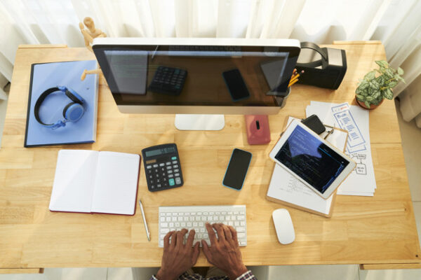 Overview of computer monitor, gadgets, papers and other supplies on wooden desk where programmer working